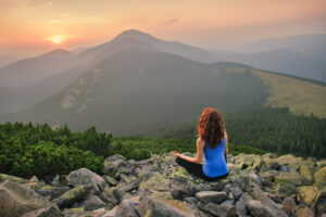 Woman feel freedom and enjoy the beautiful view in the mountains and looking on sunset
